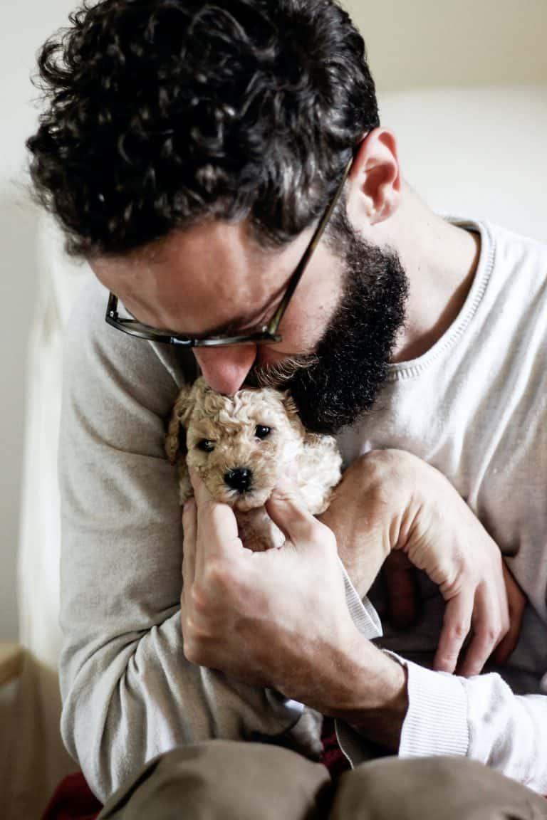 man hugging puppy